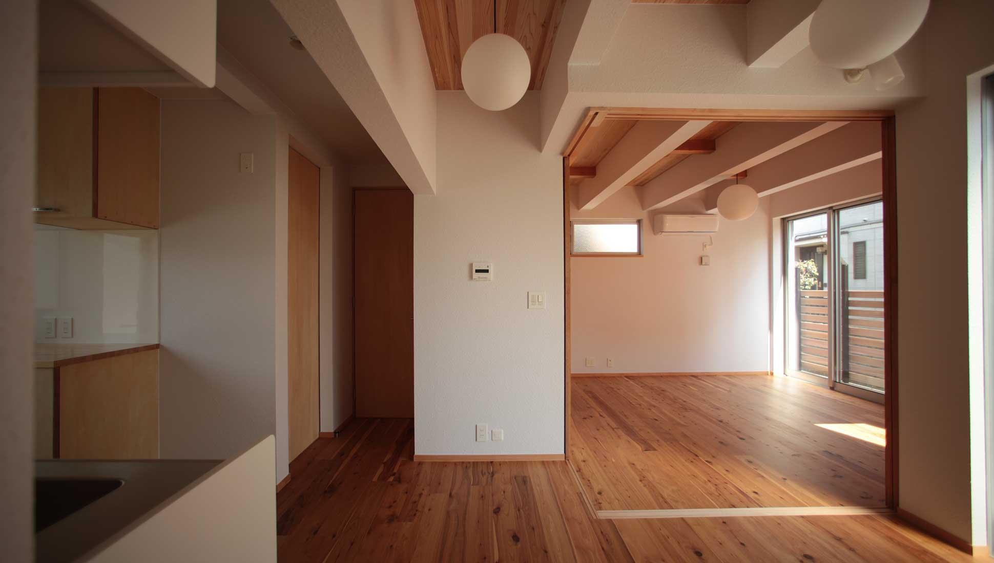 二世帯住宅の親世帯の1階リビング:Jパネルと南側階段のデザイン住宅